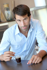 Handsome man having coffee at home