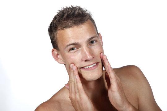 Homme appliquant un soin pour le visage