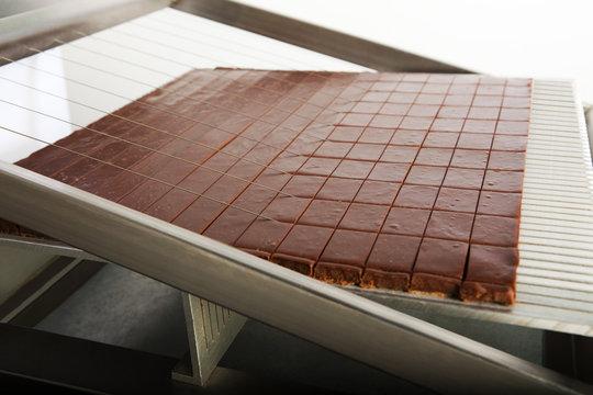 Machine découpant une plaque de barres chocolatées