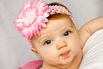 Baby girl with bright eyes posing with pink flower band