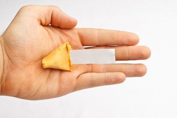 Half of a fortune cookie in a hand with a blank fortune