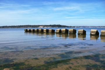 Concrete beach groyne projecting into blue sea against sky