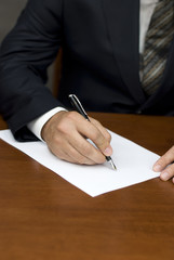 Businessman's hand writing on white sheets