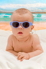 Funny baby in sunglasses on the beach