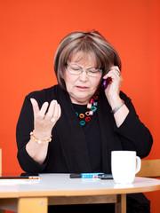 ältere Frau telefoniert mit ernster Miene