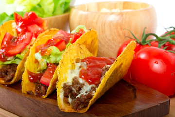 Mexican burrito in tortilla shells with fresh tomatoes.