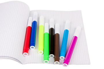 Exercise book with felt-pens isolated over white