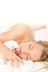 Schöne nackte Frau schläft auf weißem Bett