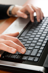 Woman hands typing on the laptop