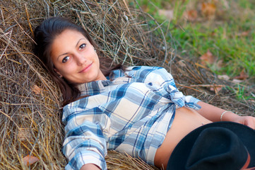 Beautiful young cowgirl lies on the pile of hay and smiles.