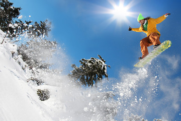 Snowboarder jumping against blue sky