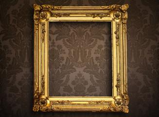 Empty golden painting frame on vintage wallpaper