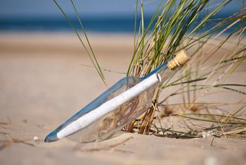 angespülte Flaschenpost vor Strandhafer
