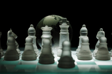 Crystal chess pieces on against a globe