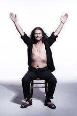 uomo seduto con braccia alzate e aperte