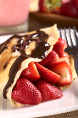 Crepe filled with fresh strawberries, chocolate sauce on top