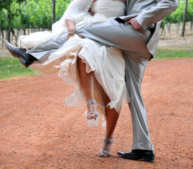 Bride and groom lifting legs on dust road