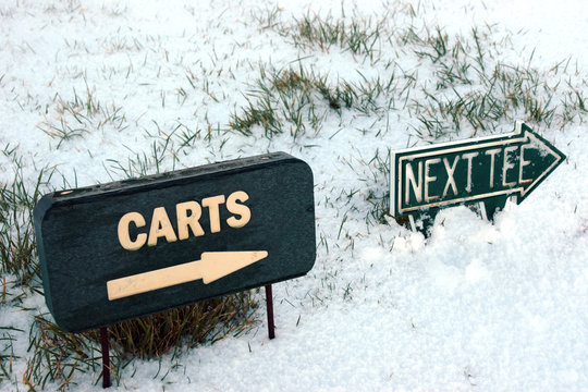 carts and next tee sign on a snow covered golf course