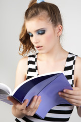 Young woman reading magazine.