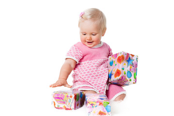 happy infant girl sitting with gift boxes isolated on white