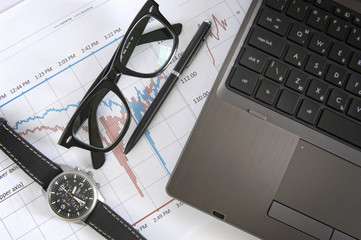 laptop, glasses, watch, pen, and informational charts