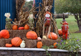Fall decorations with pumpkins, scarecrows and flowers