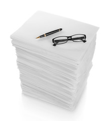 close up of pen and glasses in a stack of papers