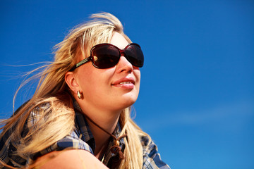 Blonde girl in skirt and sunglasses portrait on blue sky