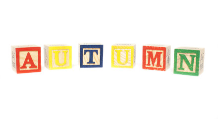 word autumn spelled with wood cubes