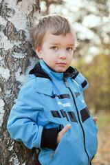 Portrait of  boy in blue jacket around birch.