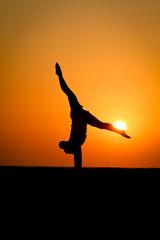 Foto op Plexiglas Rood silhouette of gymnast at beach