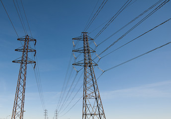 Electricity transmission power lines against a blue sky (High voltage tower). low angle view