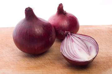 two and a half red onion on wooden desk in studio isolated