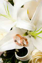 Wedding gold rings lie on a bunch of flowers for the bride