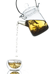Pouring tea from glass pot into mug on white background
