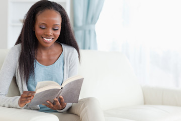 Woman on sofa with book