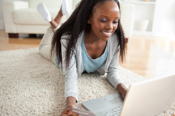 Close up of woman lying on the floor with her laptop shopping on