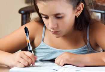Little hispanic student working on her homework