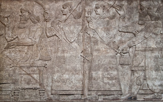 Assyrian clay relief depicting  warriors and cuneiform writing