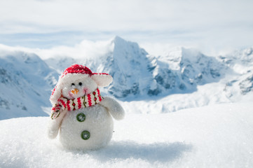 Winter holiday - happy snowman in mountains