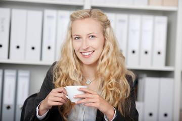 blonde frau trinkt kaffee im büro