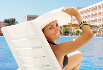Happy smiling woman in white hat near the pool