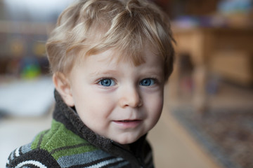 Adorable toddler boy with blue eyes and blond hairs