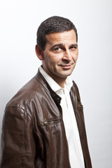 portrait of a cool mature man with leather jacket over white bac