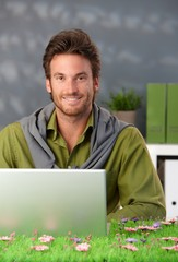 Spring portrait of smiling man with computer
