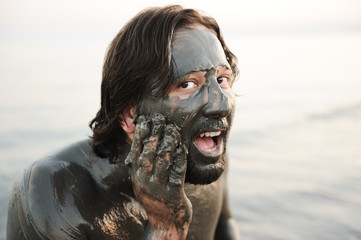 Man in a bathing of natural mineral mud from the dead sea