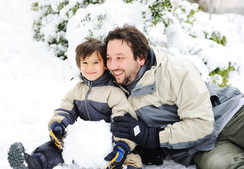 Happy father and cute son playing together on snow