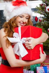 Christmas woman near a Christmas tree holding big gift box while