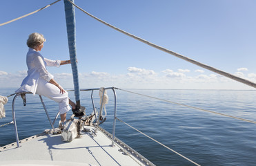 Happy Senior Woman on Bow of a Sail Boat