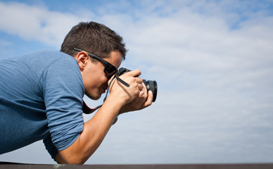 Handsome young professional photographer taking photos